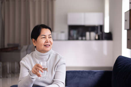 Senior asian women drinking water and sitting on sofa at home in the morning,Happy and smiling,Elderly healthy care concept Stock Photo