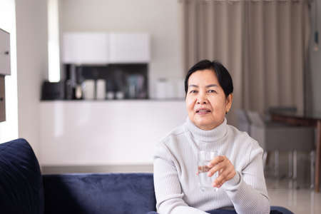 Senior asian woman drinking water at home in the morning,Happy and smiling,Elderly healthy care concept