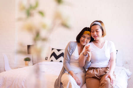Lesbian asian woman hands holding together in the bedroom ,Happy and smiling,LGBT