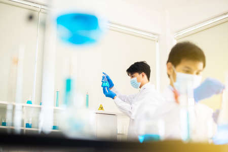 Man doctor or scientist hands holding and analyzing virus sars-cov-2 research and testing in laboratory,Covid-19,Coronavirus vaccine