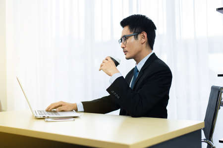 Serious asian businessman working and drinking coffee at office Imagens