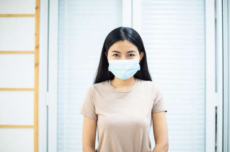 Woman wearing a mask protect PM2.5 because pollution at home,Asian female got nose allergy