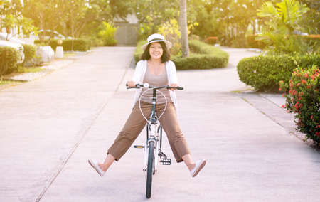 Happy asian woman cycling spreads legs on bicycle at park,Practice pedaling circles,Riding a bike