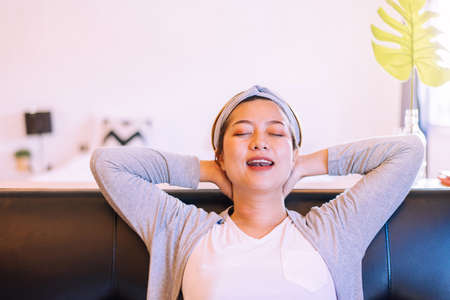 Happy asian woman sitting on couch in living room with hands over head,Comfortable sofa enjoying,Relaxing time