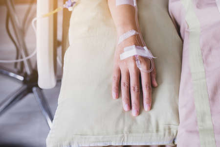 Close up of hands patient women receiving saline solution during sleeping on sick bed at the hospital