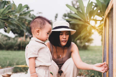 Asian mother take care baby cute boy at outdoor,Mother's day concept Imagens