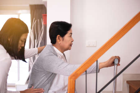 Elderly woman hands holding sticks while walking up stair at home,Caregiving take care and support,Self-Care for Family Caregivers Standard-Bild