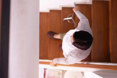 Senior woman hands holding sticks while walking up stair at home,Top view Standard-Bild