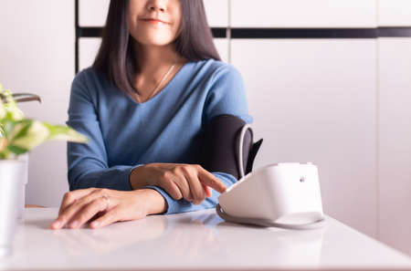Patient woman hands using blood pressure & heart rate monitors in yourself at home
