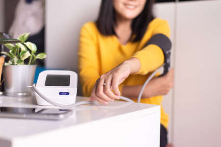 Woman using blood pressure & heart rate monitors in yourself at home