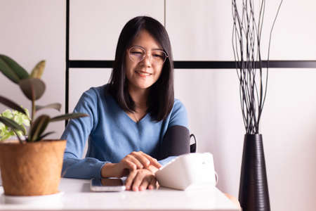 Happy asian woman using blood pressure & heart rate monitors in yourself at home Imagens