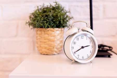 Modern alarm clock white color at the bedroom in the morning