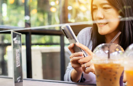 Woman using smart phone scan QR code on smart menu online to select food in restaurant