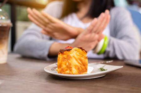 Blur of hands woman refusing cake or junk food in restaurant,No meal,Diet food concept Imagens
