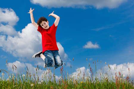 Boy jumping, running against blue sky Stock Photo - 10672016