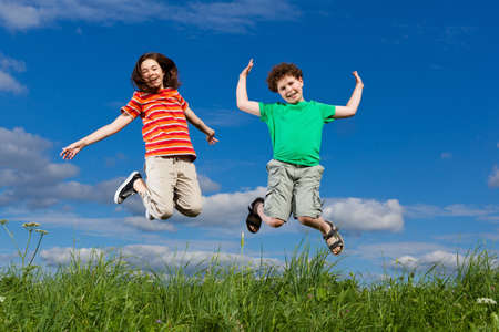 Girl and boy jumping outdoor