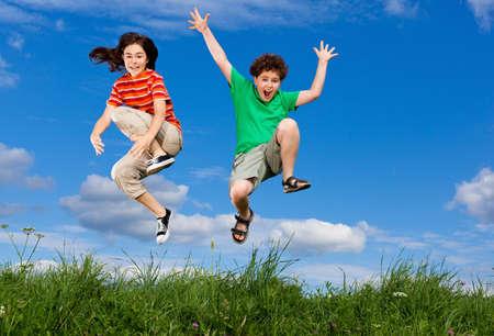 enfants qui jouent: Fille et gar�on sautant en plein air