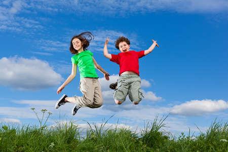 niños jugando: Niña y niño saltando al aire libre