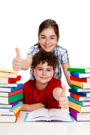 Students sitting behind pile of books on white background photo