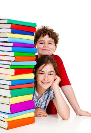 pile of books: Gli studenti seduti dietro una pila di libri su sfondo bianco