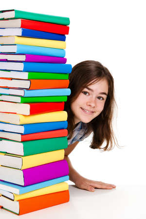 Student sitting behind pile of books on white background photo