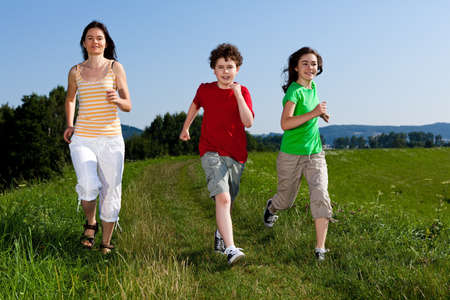 Active family - mother and kids running, jumping outdoor Stock Photo