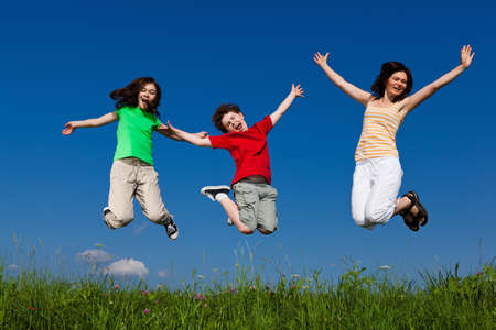 children jumping: Active family - mother and kids running, jumping outdoor Stock Photo