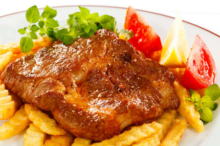 loin chops: Grilled meat, French fries ands vegetables salad Stock Photo