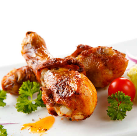 Roasted chicken drumsticks and vegetables Stock Photo