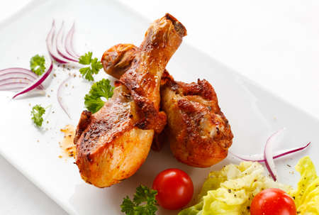 Roasted chicken drumsticks and vegetables photo