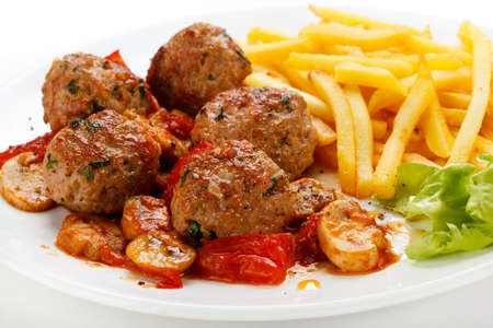french fries plate: Roasted meatballs, French fries and vegetable salad Stock Photo