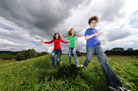 Active family - mother and kids jumping outdoor photo