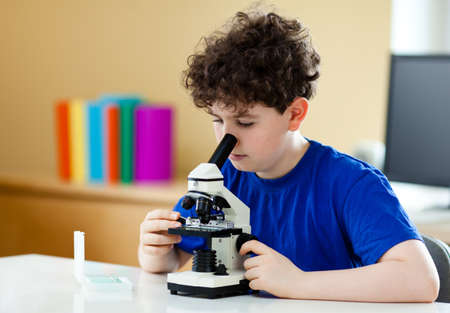 Boy examining preparation under the microscope  photo