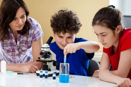Girl and boy examining preparation under the microscope  photo
