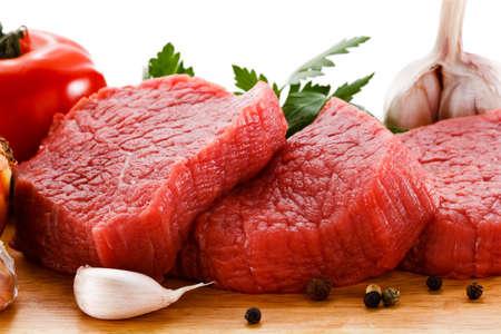 Rauw vlees op de snijplank en groenten