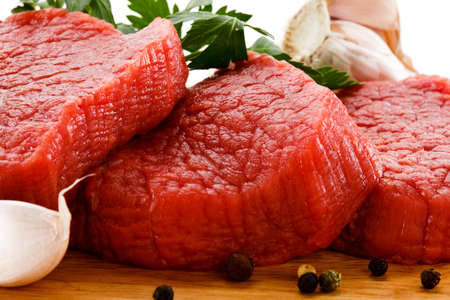 Raw beef on cutting board and vegetables photo