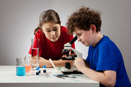 13 14 years: Girl and boy examining preparation under the microscope