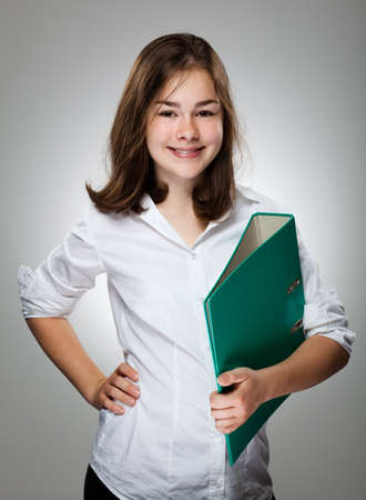 13: Girl holding book on gray background