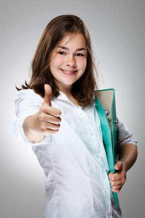 13 14 years: Girl holding book showing OK sign on gray background Stock Photo