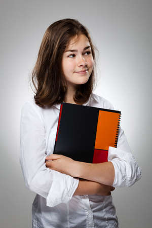 13 14 years: Girl holding book on gray background
