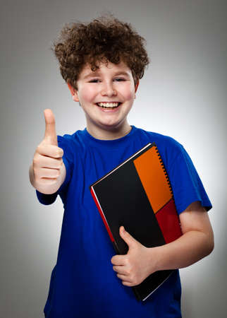 thumbs up sign: Student showing OK sign on gray background Stock Photo