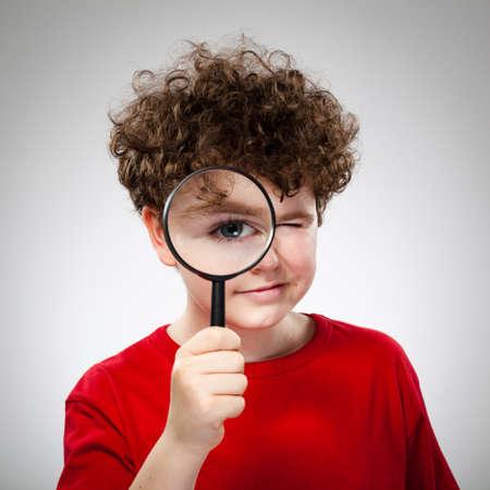 Boy holding magnifying glass Stock Photo - 13684299