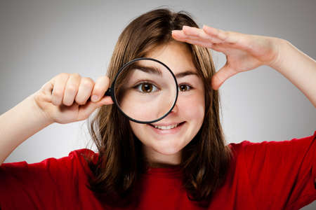 Girl holding magnifying glass Stock Photo - 13684313