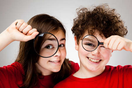 Girl and boy holding magnifying glass photo