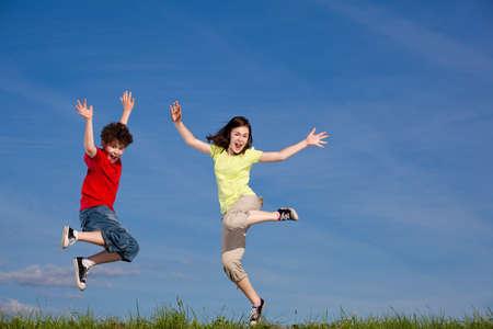 is playful: Chica y chico corriendo, saltando al aire libre
