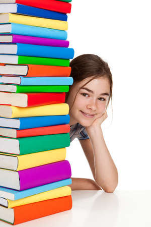 Girl peeking behind pile of books on white background photo