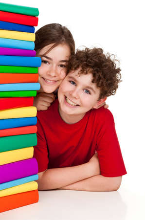 boy book: Kids peeking behind pile of books on white background
