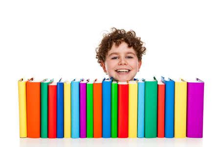 Boy peeking behind pile of books on white background photo