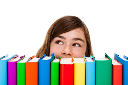 Girl peeking behind pile of books on white background