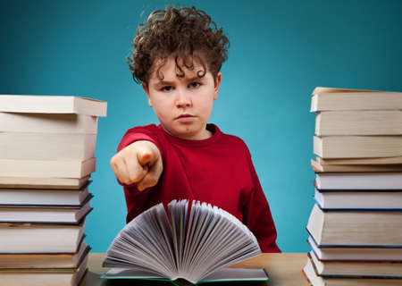 pile of books: Boy pointing